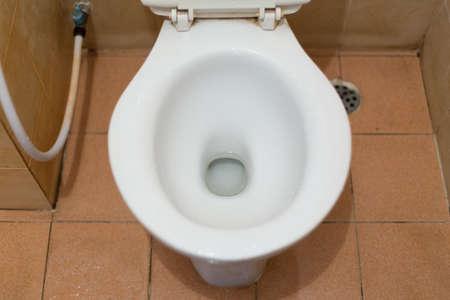 White toilet bowl on the floor tiles