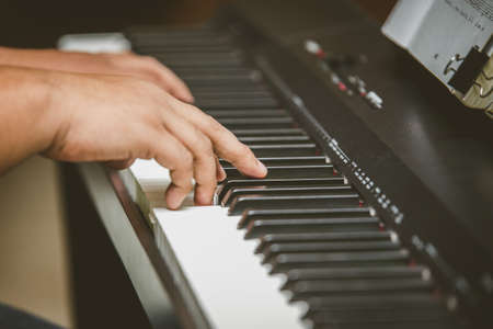 Selective focus of Man hand playing piano
