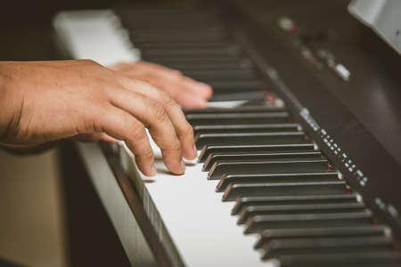 Selective focus of Man hand playing piano Foto de archivo