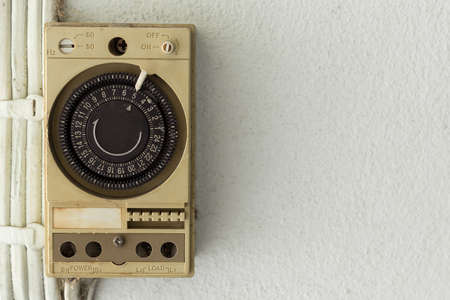 Old Electric timer on the white wall background and copy space