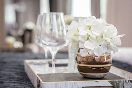Empty wine glasses and flower vases in a tray on bed