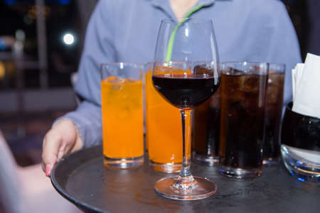 Glass drinks on the waiter's tray