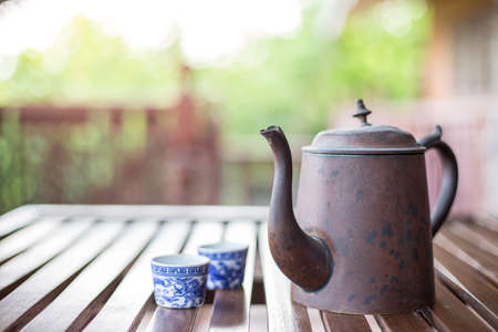 Antique Asian style tea set on a wooden table on blurred background with sunlight