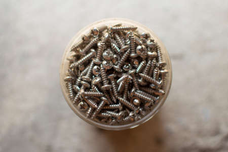 Many screws in the container on a concrete background and copy space
