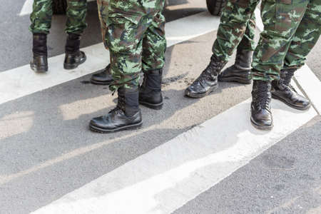 Legs of Many soldiers standing on the road