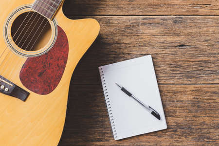 Top view of Acoustic guitar , Notebook paper and pen on wood background and copy space
