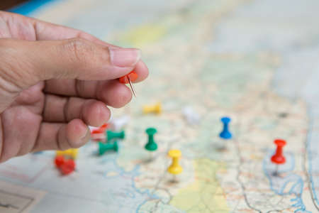 Selective focus of hand holding a pin on map background Stock Photo