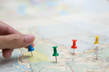 Selective focus of hand holding a pin on map background
