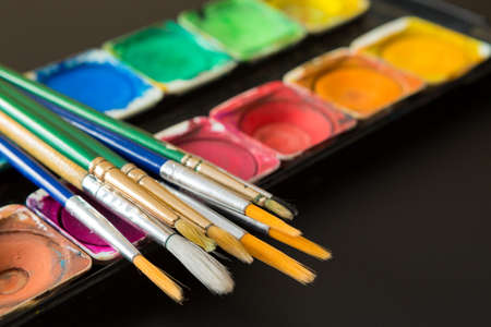 Colorful of Watercolor palette and paintbrush on a black background