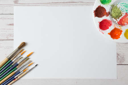 Top view of Colorful Watercolor palette, paper on a wooden table background and copy space