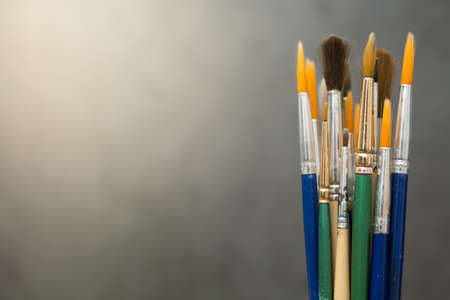 Many art brushes on a cement background with warm light and copy space 免版税图像