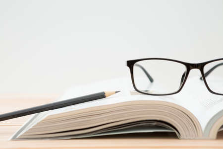 Glasses, open book, pencil on wooden table, white background and copy space 免版税图像