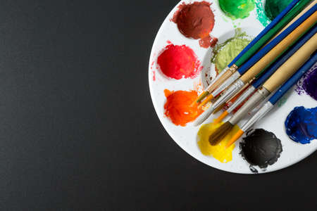 Top view of Colorful Watercolor palette and paintbrush on a black background and copy space 免版税图像