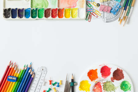 Top view of Colorful Watercolor palette, paintbrush, colored pencils, ruler and drawing equipment on white background and copy space 免版税图像