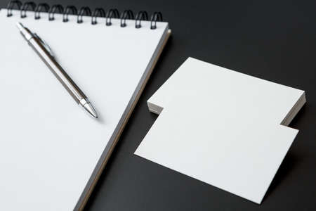 Notebooks , pen and business cards on black background 免版税图像