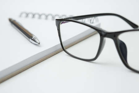 Selective focus of Notebooks, pens, glasses on white background and copy space