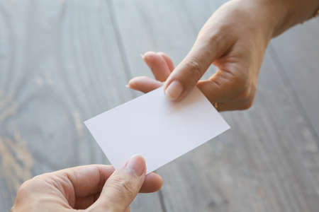 Hand holding Business card on a wood background