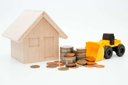 Model house, loader, coins stack on white background for money saving concept