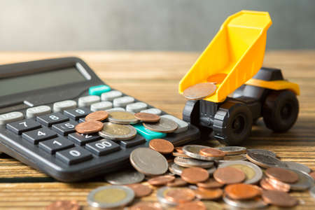 Dump truck, coins stack, calculator on wooden desks and loft walls with sunlight and copy space for money saving concept