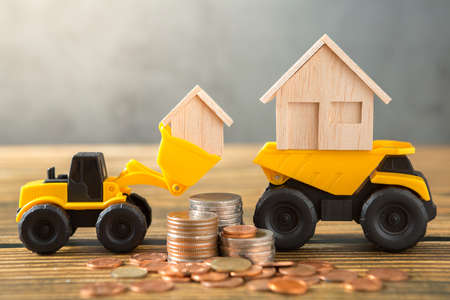 Model house in loader, Dump truck, coins stack on wooden desks and loft walls with sunlight and copy space for money saving concept 免版税图像