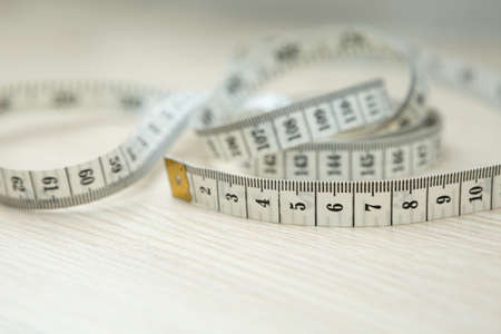 Tape measure on wood background and copy space