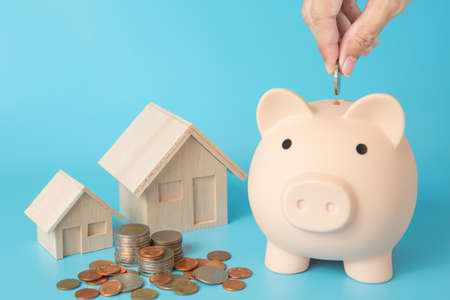 Model house, coins stack, Pig piggy, hand holding a coin bank on blue background for money saving concept