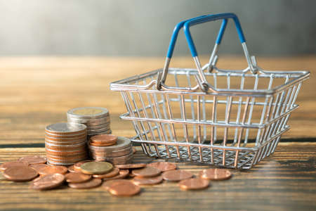Shopping basket, coins stack on wooden desks and loft walls with sunlight and copy space for money saving concept