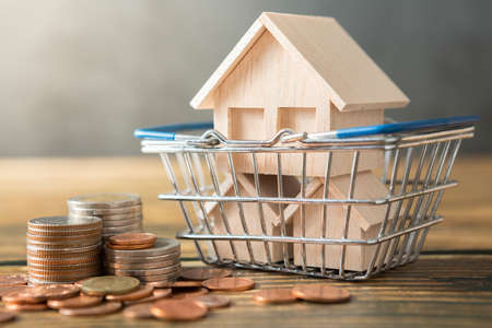 Model house in shopping basket, coins stack on wooden desks and loft walls with sunlight and copy space for money saving concept
