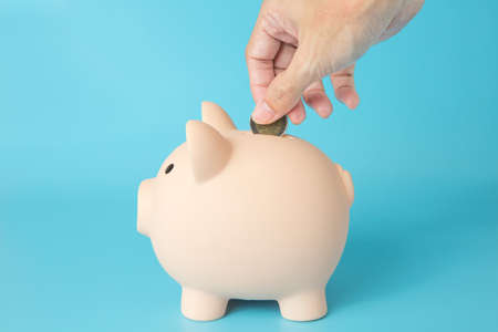 Hand holding a coin, Pig piggy bank on blue background for money saving concept
