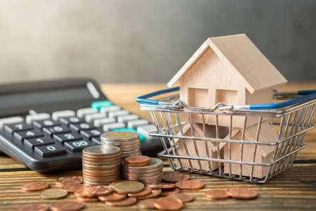 Model house in shopping basket, coins stack, calculator on wooden desks and loft walls with sunlight and copy space for money saving concept