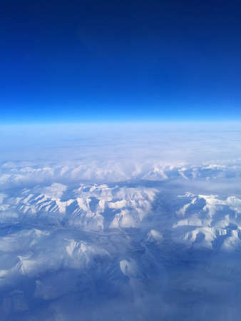 ice mountains under clouds. View from the airplane photo
