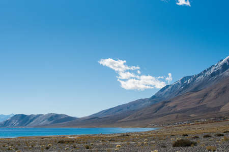 Pangong Lake in Leh Lardakh , india ,very beautiful nature scene for travel , blue salt water contrast with yellow rock mountain and clear blue sky  background .