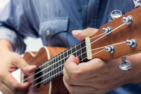 ukelele: The man is playing the brown ukulele