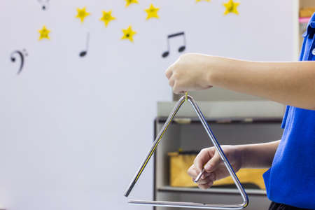 triangle musical instrument: The children is playing the triangle