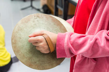 cymbal: The children is playing cymbal