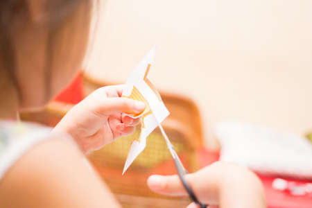 handcraft: The little girl is cutting color paper. The little girl makes handcraft.