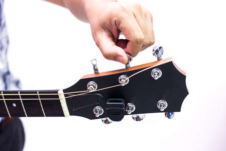 Person tuning a guitar over white background in selective focus Stock Photo