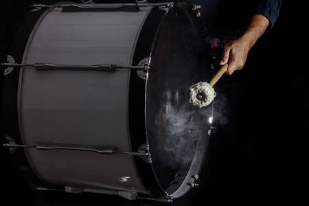 drum and bass: Drum sticks hit on the bass drum in black background, close-up, low key Stock Photo