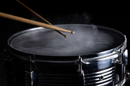 snare drum: Drum sticks hit on the snare drum in black background, close-up, low key