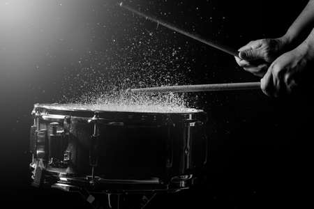 music background: The drum sticks are hitting on the snare drum with splash water in low light background Stock Photo