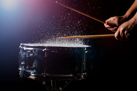 The drum sticks are hitting on the snare drum with splash water in low light background Stockfoto