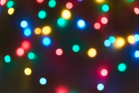Blurred bright bokeh lights on black background, against blurred bright background,Christmas and New Year Holiday firework.Bright abstract background ideal for any design