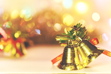 christmas bell decoration with bokeh lights on white background against blurred bright background xmas