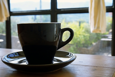 Black cup with steaming hot coffee on the wooden table with blurred green garden background, Wood over summer window background
