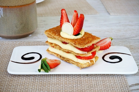 Mille-feuille on white plate, thats the French desserts, is a stack of pie crust, custard cream and fresh strawberry then topped with strawberry and white chocolate.