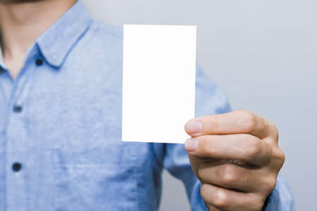 Person holding a white business card on a white background, vertical, template, blue shirt, business man.Business Concept