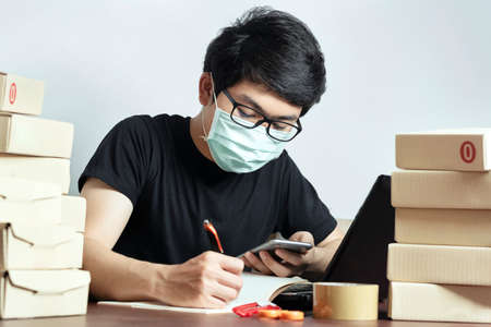 Asian man small business owner and Wear a mask to protect against Corona virus. Work from home, Have a laptop, and a smartphone recording the product information Online marketing, Startup SME Stock Photo