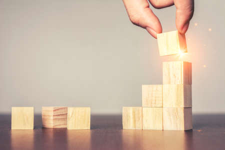 Hand arranging wood block stacking as step stair on table.New normal Business development Decide and choose, Business concept for growth success process,Vintage tone.Copy space
