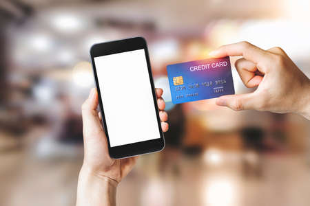 Hands holding credit card with Smart mobile phone show white background for product mockup over for online shopping on shopping mall background, E-payment technology, Concept of internet banking