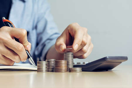 Businessmen are using pens to Record the amount of Money coins for Plans to Accountancy on wood table stack in office at home, with copy space.Accounting and financial economic calculation concepts.